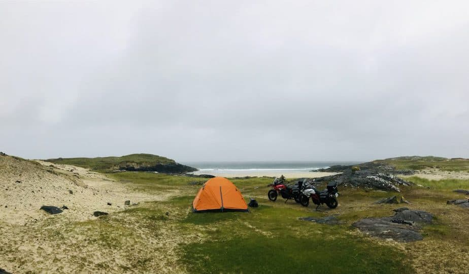 a tent and motorcycles camping on the beach