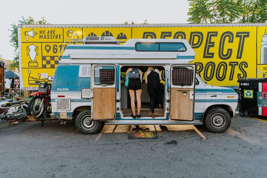 two girls looking inside a vintage van